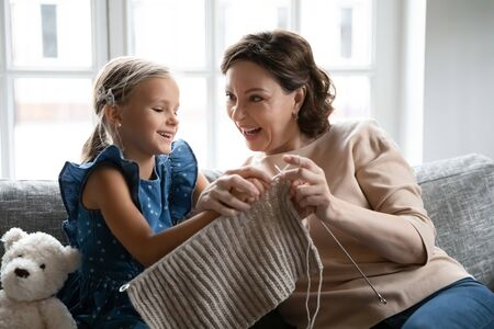 Smiling middle-aged 60s grandmother sit on sofa have fun teach little granddaughter knitting with needles, happy mature granny relax on couch in living room, engaged in hobby activity on weekend