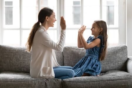 Overjoyed young mom and small daughter sit on sofa in living room play pat a cake hand clapping game together, happy mother and little preschooler girl child have fun enjoy family weekend at home