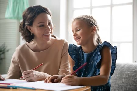 Caring middle-aged 60s grandmother sit at desk preparing homework handwriting with little granddaughter, loving senior granny study with small grandchild drawing painting together at home