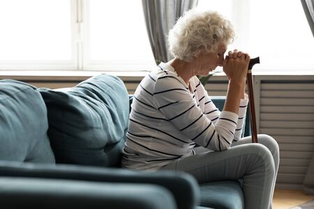 Side view exhausted older mature grandmother sitting on sofa with walking wooden cane in hands, feeling depressed at home. Retired unhappy senior woman suffering from disability alone in living room. Stock fotó