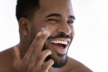 Close up portrait of happy young african American man apply moisturizing face cream for healthy glowing skin, smiling millennial biracial male use nourishing facial balm, skincare, hygiene concept
