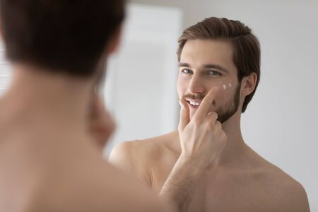 Smiling young Caucasian man look in mirror in bathroom apply moisturizing facial cream for healthy glowing skin, millennial male use nourishing face anti-wrinkle balm product, skincare concept