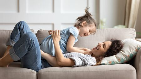 Happy laughing mother with little daughter relaxing on cozy couch in living room, smiling young mum and cute preschool girl cuddling, tickling, having fun together, spending lazy weekend at home