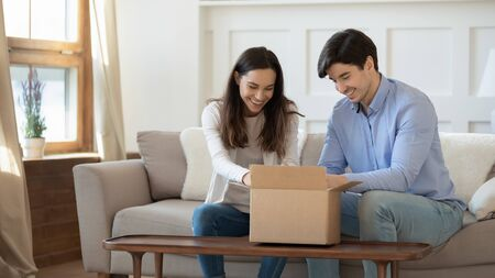 Happy young caucasian couple sit on sofa at home feel excited unpacking cardboard postal package together, smiling man and woman unbox internet order shipment, buying goods shopping online
