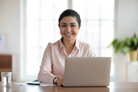 Head shot portrait young smiling indian woman sitting at table with computer. Happy hindu businesswoman professional looking at camera, spending time at workplace with laptop in modern office. Stock Photo