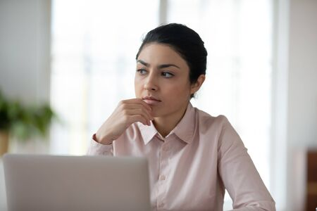 Head shot lost in thoughts young indian woman sitting in front of computer, looking away. Thoughtful millennial professional solving problems, finding inspiration, thinking over hard decision.