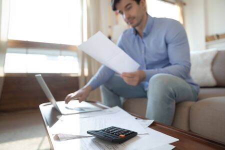 Close up focus of young man pay bills taxes on laptop online, consider post financial paperwork at home, concentrated male manage household finances expenditures, saving, investment concept