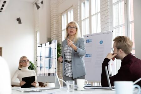 Focused middle aged female boss leader speaker standing at table near whiteboard, explaining company marketing strategy to concentrated young colleagues at brainstorming meeting in modern office.