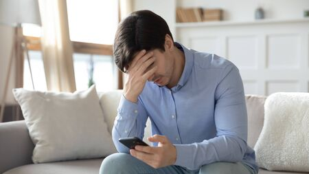 Upset young man sit on sofa at home frustrated by negative message on smartphone gadget, unhappy male distressed by eviction notice email or bad news on cellphone, get cell problems or virus