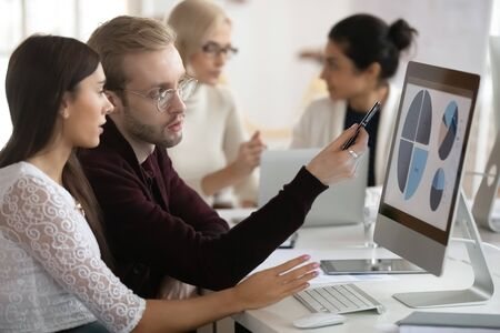Side view serious young blonde businessman in glasses pointing at graphs on monitor, discussing marketing strategy with young female colleagues. Motivated coworkers working on presentation in office. Standard-Bild