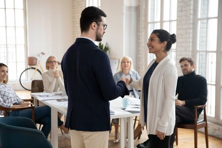 Confident male team leader shaking hands with young indian female colleague, congratulating with personal success praising promoting at employees meeting in modern office, thanking for good job. Standard-Bild