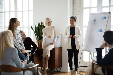 Young focused indian female speaker coach standing near whiteboard, giving marketing research results presentation or training to focused diverse colleagues employees businesspeople in modern office.
