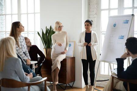 Jeune coach de haut-parleurs indiens concentrés debout près du tableau blanc, donnant une présentation des résultats de la recherche marketing ou une formation à divers collègues concentrés, employés, hommes d'affaires dans un bureau moderne.