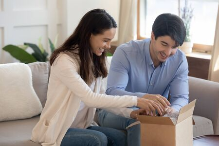 Happy young caucasian couple sit on sofa at home unpack cardboard package with internet order, smiling man and woman unbox web shipment post box from delivery service, shopping online together