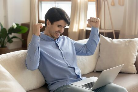 Excited young caucasian man sit on sofa in living room triumph read pleasant news in email letter on laptop, overjoyed male feel euphoric winning online lottery on modern computer, luck concept Stock fotó
