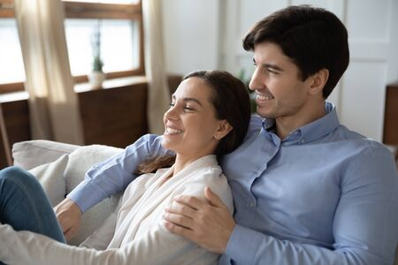 Happy young caucasian couple sit cuddle on couch in living room enjoy tender romantic leisure weekend dreaming together, smiling loving man and woman relax on sofa at home hugging and embracing