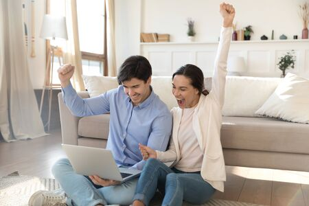 Overjoyed young couple sit in living room feel excited euphoric win online lottery on laptop, happy Caucasian man and woman triumph get good pleasant email using computer at home together
