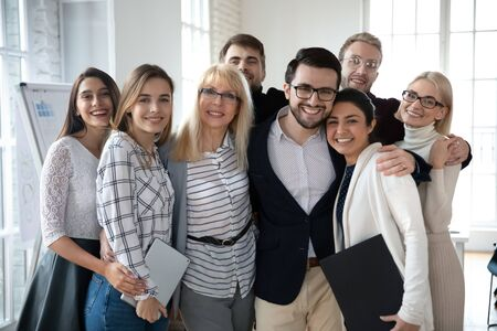 Portrait of emotional positive bonding diverse business people, posing for photo in office. Overjoyed excited friendly young and middle aged mixed race teammates embracing, looking at camera.