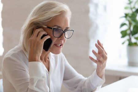 Angry senior female employee in glasses argue with client or customer talking on smartphone, mad frustrated middle-aged businesswoman feel distressed dispute solve problem over cellphone call Foto de archivo