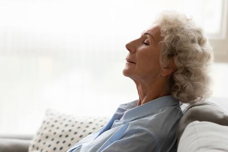 Side view peaceful grey-haired old woman leaned rests on couch reduces fatigue feels serenity breathing fresh conditioned air, no stress lifestyle, retired life, repose deep inner relaxation concept