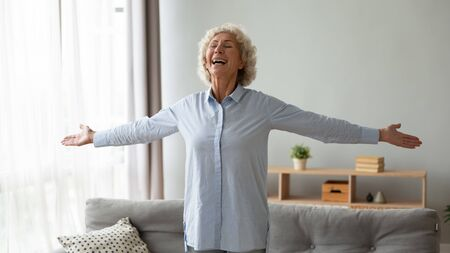 Lively hoary 65s aged woman stands in modern living room stretched hands feeling happiness and rejoice dancing listening music spend time at home. Enjoyment of healthy retired life and new day concept