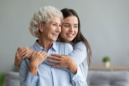 Young caring grand daughter hugging to loving elderly grandmother, multi-generational relatives women standing look in window dreaming feels happy spend time together, love connection warmth concept Stock fotó - 149460590