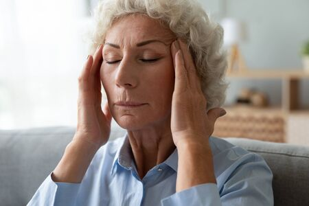 Close up face of elderly 65s woman massaging temples closed eyes reduces intense intermittent throbbing headache chronic terrible migraine, hormonal imbalance, high blood pressure hypertension concept