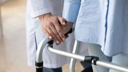 Physical therapist helping to female old patient walking with rollator close up image. Neurological or musculoskeletal disorders of older people, supportive equipment, nursing and elder care concept
