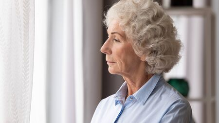 Gray haired contemplative 70s woman looking out the window thinking lost in sad thoughts goes through loneliness, senile diseases dementia or mental problems, being in nostalgia life memories concept