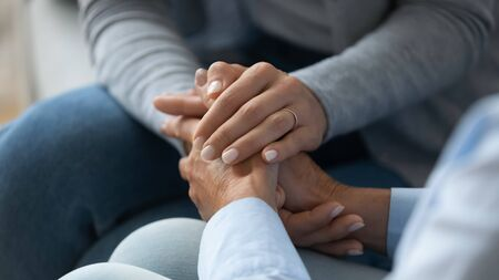 Adult daughter comforting old mom strokes holds her hand close up view. Strong connection confidential conversation, empathy and mercy, support in hard life period, be near sharing heart pain concept Foto de archivo