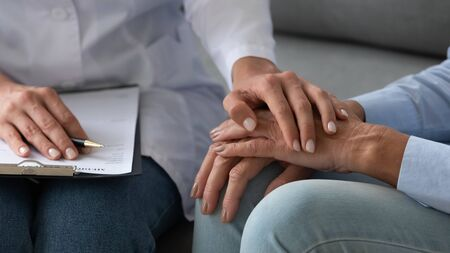 Seated on couch social service homecare nurse worker in white coat supports old patient hold hand encourages her close up, cancer diagnose, overcome illness, psychological help express empathy concept Stock fotó - 149361958