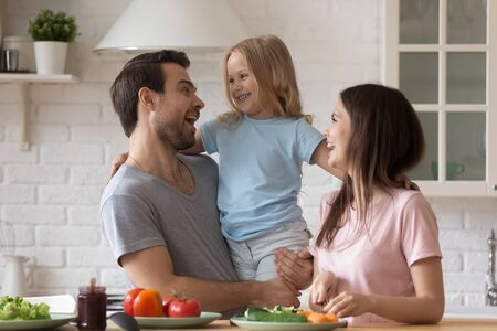 Overjoyed young family with small daughter have fun cooking together on modern kitchen, happy parents feel excited preparing breakfast healthy food with little girl child at home on weekend