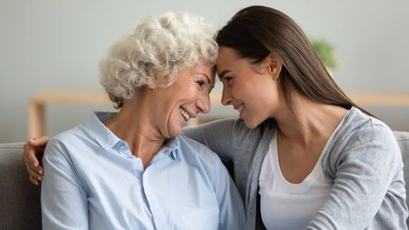 Close up profile faces multi-generational women sit on sofa adult granddaughter and elderly grandmother hugging touch foreheads looking each other smiling enjoy time talk together showing love concept Stock fotó - 149361975