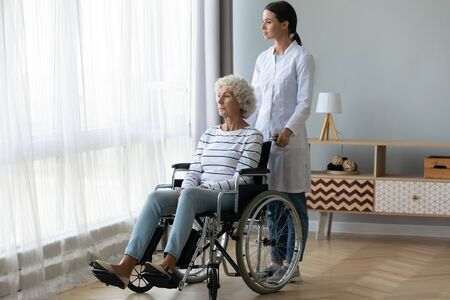 Sad handicapped elderly woman sitting in wheel chair looking in window feels miserable suffers from disease near standing caregiver young attractive woman in white coat, eldercare and nursing concept