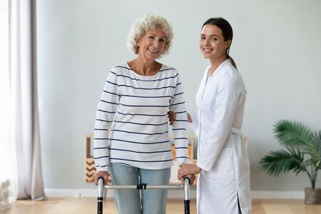 Elderly grandma holding walking frame feels satisfied after rehabilitation exercise therapy with female physical therapist, women smile look at camera. Caregiving, elder care and physiotherapy concept