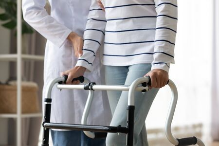 Cropped image caregiver helping to disabled patient walking with rollator equipment reduce load and joint pain with arthritis. Physical therapist and therapy, neurological cerebellar disorders concept