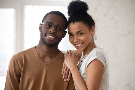 Head shot happy African ethnicity spouses portrait concept. Newly weds pose in rented flat, bank approved loan for young family. Pretty wife snuggles to husband in glasses people smile look at camera