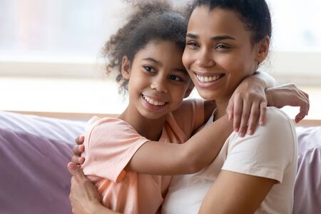 Beautiful mixed-race mother hugs adorable African daughter family enjoy tender moment feels excited sitting together on couch at home. Offspring, happy motherhood love and parental protection concept