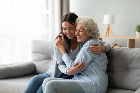 Happy multi-generational family sitting on couch in living room, elderly grandmother snuggle to grown up granddaughter, adult daughter missed mature mom, holidays, events, Mother Day congrats concept 免版税图像