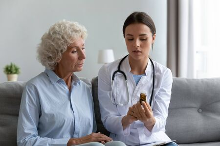 In living room young female caregiver practitioner nurse in white coat stethoscope on shoulders seated on couch explain to old patient pills dosage, social care, problem prevention, geriatric medicine