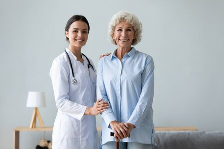Elderly woman patient holds walking stick photo shooting with young caregiver practitioner in white coat portrait in living room, successful physiotherapy after accident, homecare and nursing concept
