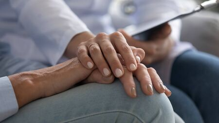 Close up image, female nurse holding hand of elderly woman patient provides professional psychological support helping overcome bad news about fatal diagnosis, dementia senile disease health problems