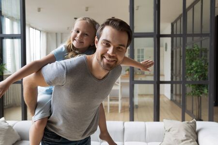 Portrait of excited little girl piggyback young father playing together at home, happy loving dad feel playful engaged in funny game carry on back overjoyed small daughter, family weekend concept