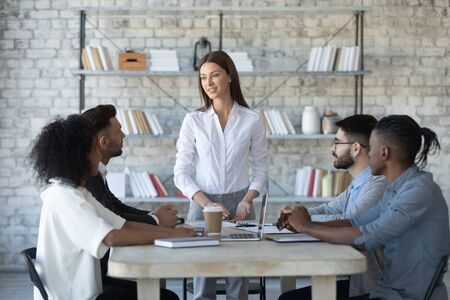 Confident businesswoman team leader speaking at corporate meeting, holding briefing with diverse colleagues, employees sharing ideas, mentor coach training staff, business partners negotiation