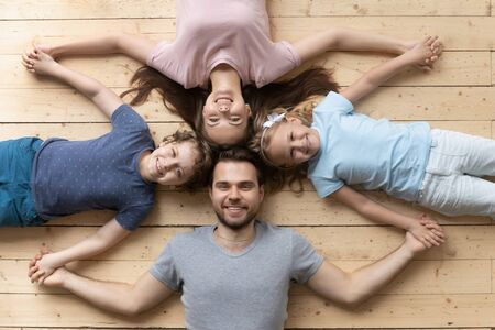 Top view portrait of smiling young family with little children lying on warm wooden floor holding hands together, happy parents with small preschooler kids show unity and support, bonding concept