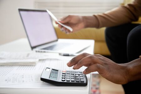 Manage planning family budget, savings and payment concept. Close up image hands of African man using calculator calculates finances checking family expenses, do small business, month result analysis