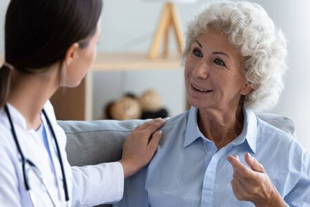 Caregiving and eldercare, provide mental or physical care for older generation, homecare and nursing concept. Elderly grey haired woman patient talk tell health complaints to young medic in white coat