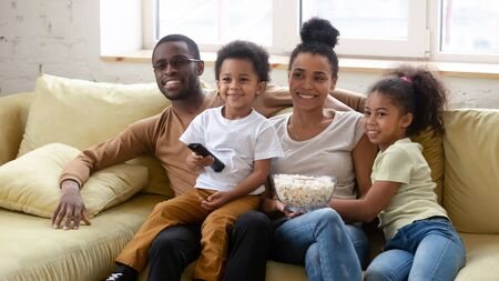 African spouses and little pretty kids spend lazy weekend together seated on couch in living room eating pop-corn choosing show or movie on TV. Happy family activity at home, free time and fun concept
