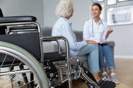 Physical therapist woman in white coat talk to elderly woman disabled patient client seated on sofa in living room, close up focus on wheelchair. Concept of handicapped person, caregiving and homecare Banque d'images