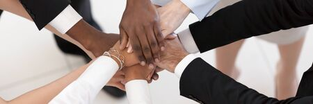 Close up top above view group of multi ethnic business people stacked palms together as concept of corporate unity, connection, team building loyalty. Horizontal photo banner for website header design